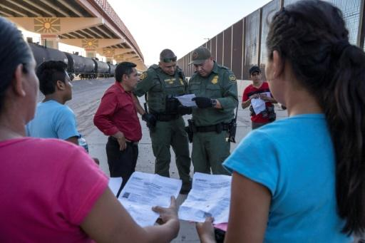 US Customs and Border Protection agents in May 2019 check documents in El Paso, Texas, from a small group of migrants who crossed from Mexico