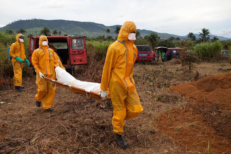 Volunteers in protective suit carry for burial the body of a person who died from Ebola in Waterloo, southeast of Freetown, on October 7, 2014