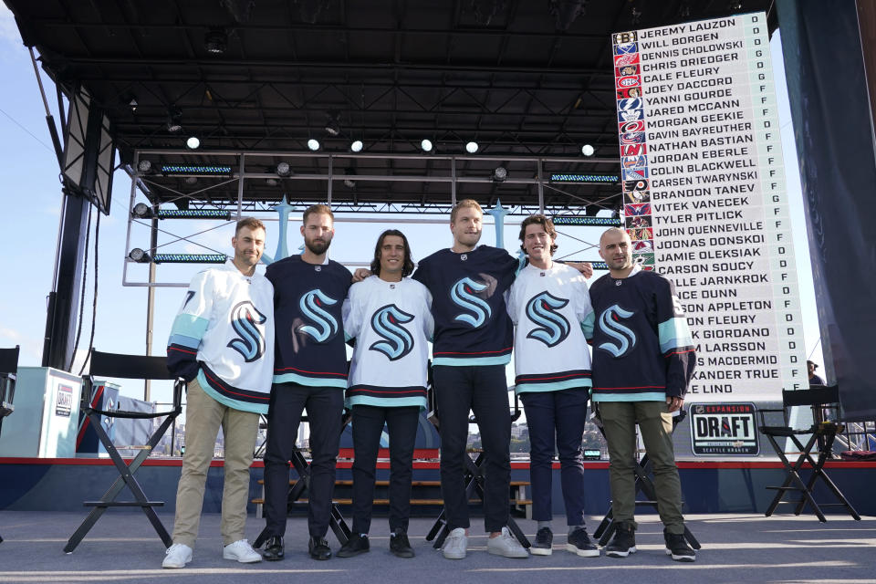 Seattle Kraken NHL hockey players Jordan Eberle, Chris Dreidger, Brandon Tanev, Jamie Oleksiak, Hadyn Fluery and Mark Giordano, from left, pose for a photo Wednesday, July 21, 2021, after being introduced during the Kraken's expansion draft event in Seattle. (AP Photo/Ted S. Warren)