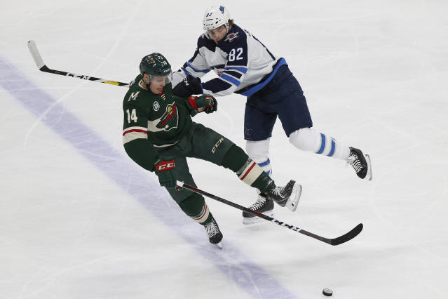 Minnesota Wild's Joel Eriksson Ek, of Sweden, and Winnipeg Jets' Mason Appleton look toward the puck in the third period of an NHL hockey game Thursday, Jan. 10, 2019, in St. Paul, Minn. (AP Photo/Stacy Bengs)