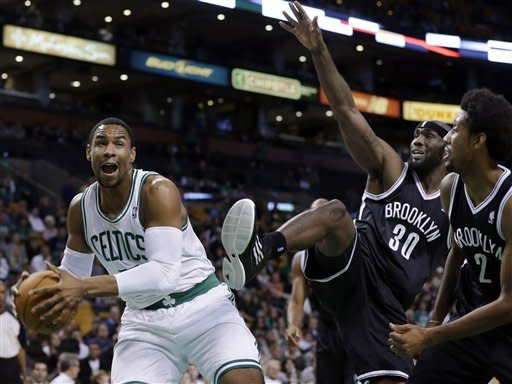 Boston Celtics' Jared Sullinger, left, brings down an offensive rebound against Brooklyn Nets' Reggie Evans (30) and Josh Childress (2) during the first half of an NBA preseason basketball game in Boston, Tuesday, Oct. 16, 2012. (AP Photo/Elise Amendola)
