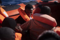 A migrant smiles as he is assisted with others by aid workers of the Spanish NGO Open Arms, after fleeing Libya on board a precarious wooden boat in the Mediterranean sea, about 110 miles north of Libya, on Saturday, Jan. 2, 2021. (AP Photo/Joan Mateu)