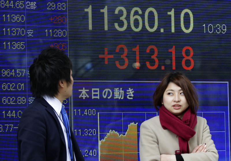 A man watches an electronic stock indicator of a securities firm as a woman stands by him in Tokyo, Wednesday, Feb. 6, 2013. Shares were mostly higher in Asia early Wednesday, tracking gains in the U.S. and Europe, as the Japanese yen pushed sharply higher. The Nikkei 225 stock index gained 3 percent, or 329.98, to 11,376.90 as exporters shares soared on expectations of stronger sales thanks to the yen's gains against other major currencies. (AP Photo/Shizuo Kambayashi)