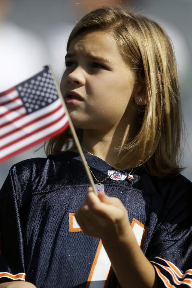 Kaitlyn Speck waves an American flag before an NFL football game between the Chicago Bears and Atlanta Falcons in Chicago, Sunday, Sept. 11, 2011. (AP Photo/Nam Y. Huh)