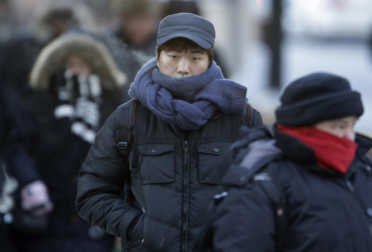 Commuters bundle up against extreme cold conditions Tuesday, Jan. 22, 2013, in Chicago. Temperatures in the area were hovering around zero with sub-zero wind chill reading hitting 10 below. Forecasters say waves of frigid Arctic air began moving over the region Saturday night Jan. 19, 2013. Temperatures are expected to rebound Wednesday Jan. 23, 2013. (AP Photo/M. Spencer Green)