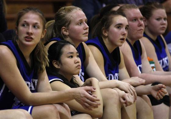 Joy Cheng (2nd L), a foreign exchange student from Taipei, Taiwan, sits on the bench with her teammates from the Grant-Deuel School Girls' junior varsity basketball team during a game in Waverly, South Dakota February 14, 2012.