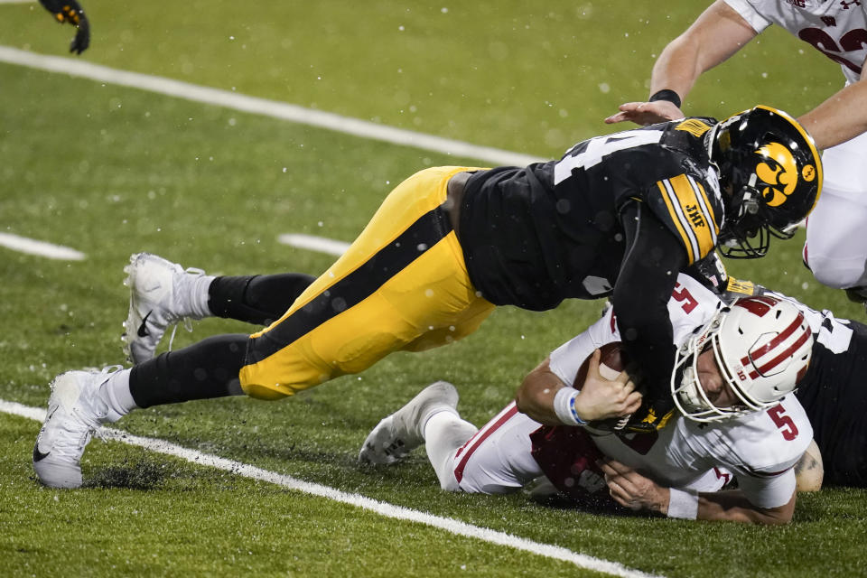 Wisconsin quarterback Graham Mertz (5) is tackled by Iowa defensive tackle Daviyon Nixon, left, during the second half of an NCAA college football game, Saturday, Dec. 12, 2020, in Iowa City, Iowa. Iowa won 28-7. (AP Photo/Charlie Neibergall)