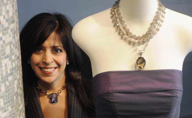 """FILE - In this Dec. 30, 2008 file photo, fashion designer Maria Pinto is seen in her boutique in Chicago. Pinto, famous for dressing first lady Michelle Obama and Oprah Winfrey, used her eye for fashion to curate Field Museum antiquities for a new exhibit that includes a century-old shredded bark Brazilian ceremonial costume and a woven monkey fur necklace. The exhibit """"Fashion and The Field Museum Collection: Maria Pinto"""" opens Friday, Sept. 14, 2012. (AP Photo/David Banks, File)"""