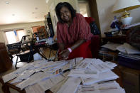 Debra Smith, 57, sits with her medical bills in her living room on Thursday, Oct. 7, 2021, in Spring Hill, Tenn. Smith, who has health problems that prevent her from working, has about $10,000 in unpaid medical bills. Living expenses and prescriptions consume most of the $2,300 a month she gets from a pension and Social Security. (AP Photo/Mark Zaleski)