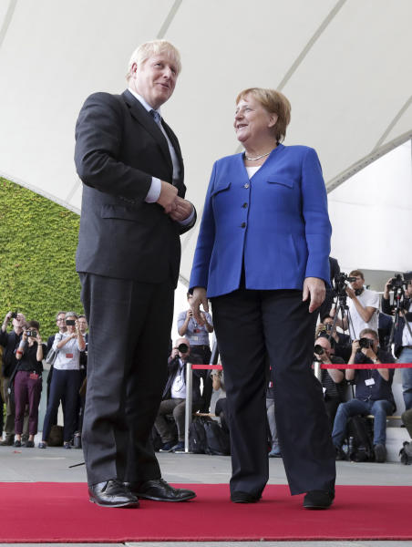 German Chancellor Angela Merkel welcomes Britain's Prime Minister Boris Johnson during a welcome ceremony with military honors for a meeting at the Chancellery in Berlin, Germany, Wednesday, Aug. 21, 2019. (AP Photo/Michael Sohn)
