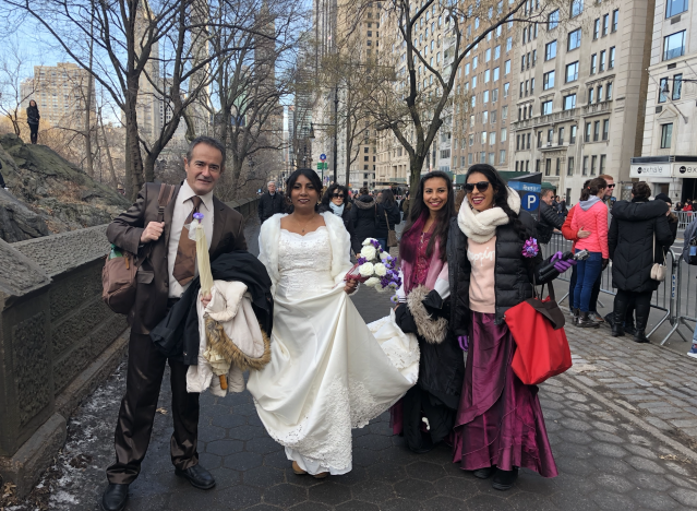 Cochan Yves and his brand new bride, Virginie Valeama, pass the march on their way to take wedding photos in Central Park. (Photo: Lisa Belkin/Yahoo News)