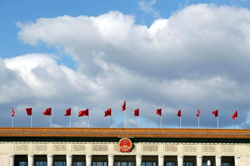 Red flags flutter on the top of the Great Hall of the People in Beijing