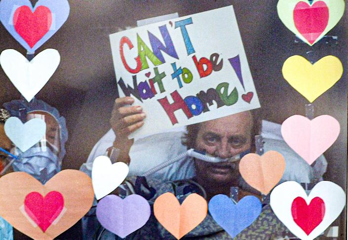 "Richard Frady, a recovering COVID-19 patient in the intensive care unit at AnMed Health in Anderson, S.C., waves a ""Can't Wait to be Home!"" sign on his 32nd day after diagnosis to his wife, Sally, and daughter Allison Nissen from his window at the hospital April 28."