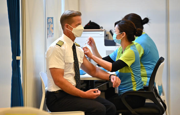 A Cathay Pacific pilot receives China's Sinovac COVID-19 coronavirus vaccine at a community vaccination centre in Hong Kong Tuesday, Feb. 23, 2021. Frontline workers and high risk people are the first in line to be vaccinated in the territory.(Peter Parks/Pool Photo via AP)