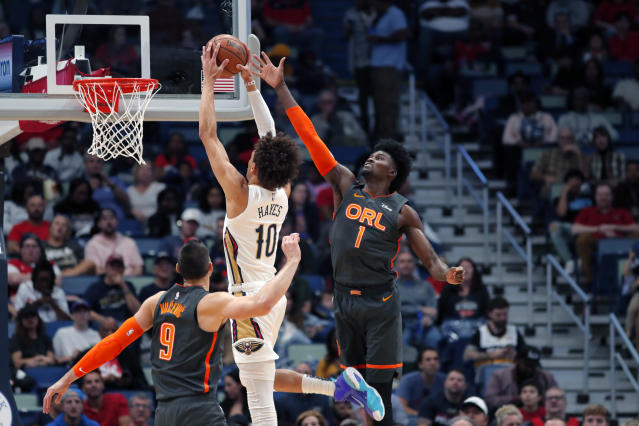 New Orleans Pelicans center Jaxson Hayes (10) goes to the basket between Orlando Magic center Nikola Vucevic (9) and forward Jonathan Isaac (1) in the first half of an NBA basketball game in New Orleans, Sunday, Dec. 15, 2019. (AP Photo/Gerald Herbert)