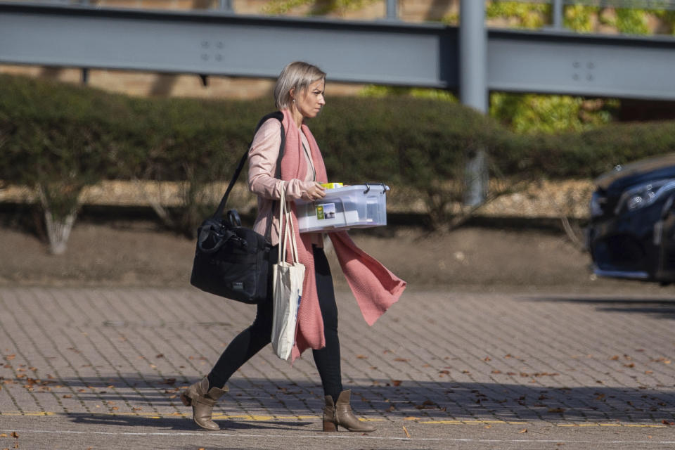 People leaving the headquarters of tour operator Thomas Cook, in Peterborough, England, which has ceased trading with immediate effect after failing in a final bid to secure a rescue package from creditors Monday Sept. 23, 2019. British tour company Thomas Cook collapsed early Monday after failing to secure emergency funding, leaving tens of thousands of vacationers stranded abroad. The British government said the return of the 178-year-old firm's 150,000 British customers now in vacation spots across the globe would be the largest repatriation in its peacetime history. (Joe Giddens/PA via AP)