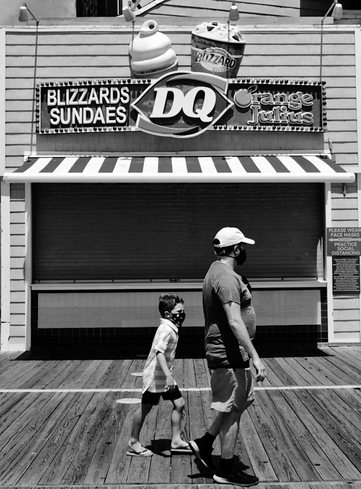 Two people wearing masks on the boardwalk pass a closed Dairy Queen store.