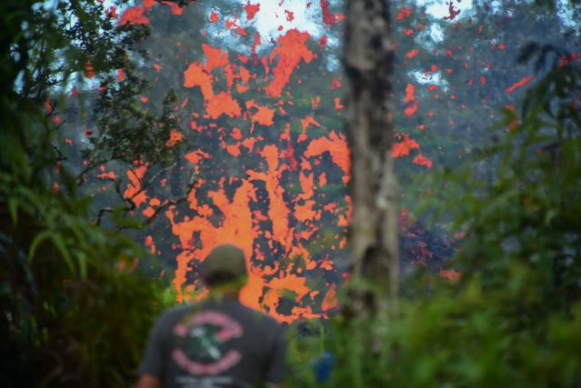 <p>A man watches as lava is seen coming from a fissure in Leilani Estates subdivision on Hawaii's Big Island on May 4, 2018. (Photo: Frederic J. Brown/AFP/Getty Images) </p>