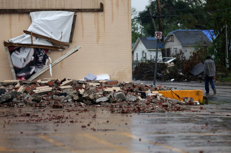 FILE PHOTO: A man walks past a building that was damaged by Hurricane Laura as Hurricane Delta approaches in Lake Charles
