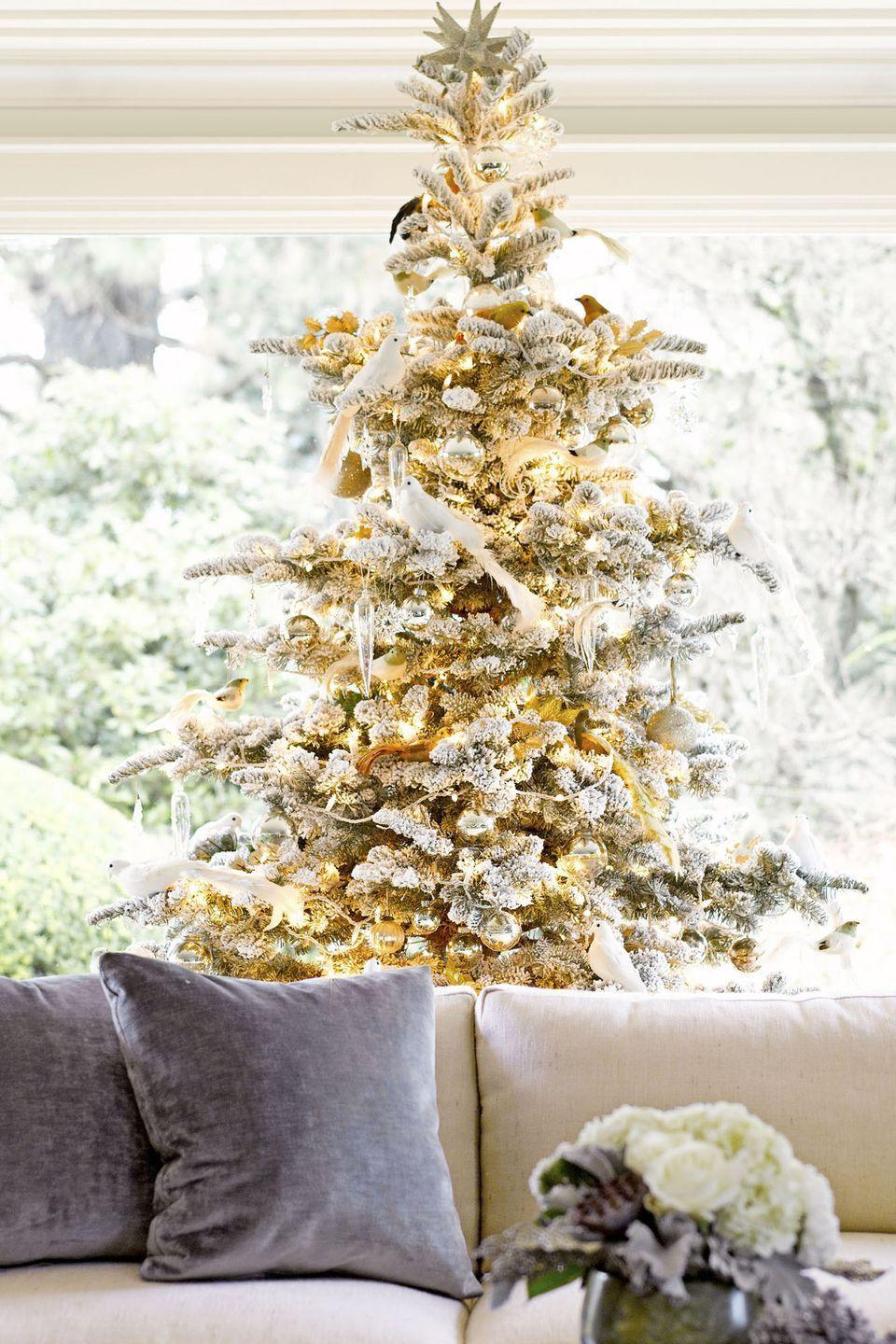 """<p>For an understated (but totally glamorous) option, spruce up a snow-covered pine with white doves, twinkle lights, and gold baubles. </p><p><strong>RELATED: </strong><a href=""""https://www.goodhousekeeping.com/holidays/christmas-ideas/g29022426/best-white-christmas-trees/"""" rel=""""nofollow noopener"""" target=""""_blank"""" data-ylk=""""slk:14 Best White Christmas Trees"""" class=""""link rapid-noclick-resp"""">14 Best White Christmas Trees</a></p>"""
