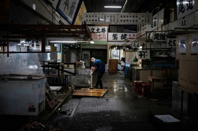 A fishmonger cleans his shop at the Tsukiji fish market one last time