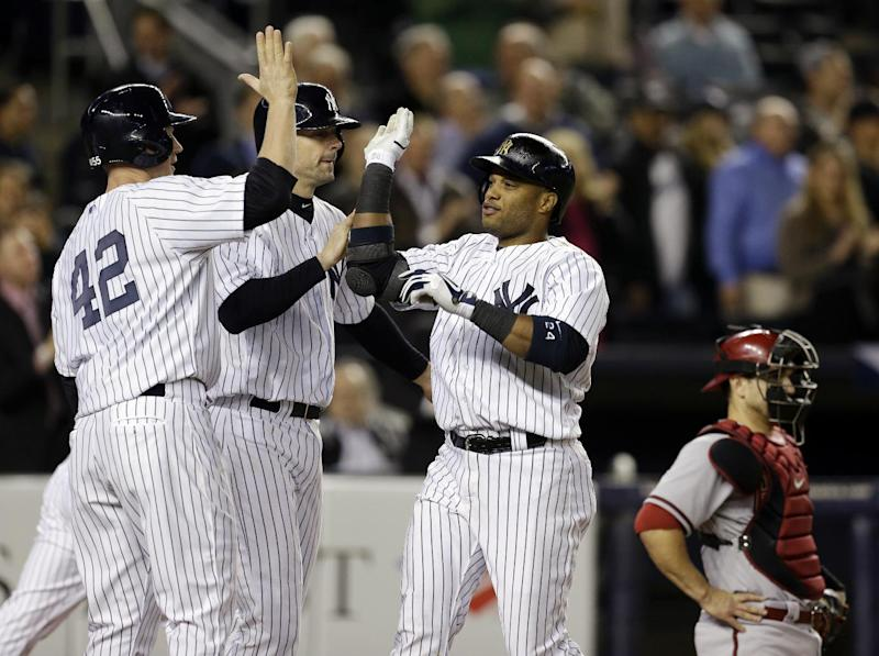 New York Yankees' Lyle Overbay, left, and Chris Stewart greet Robinson Cano at the plate after they scored on Cano's fourth-inning, three-run home run in a baseball game at Yankee Stadium in New York, Tuesday, April 16, 2013. Arizona Diamondbacks catcher Miguel Montero is at far right. (AP Photo/Kathy Willens)
