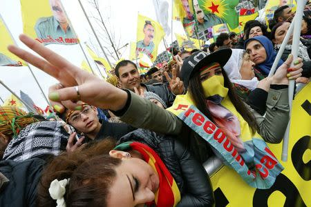 People carry flags during a demonstration organised by Kurds, in Frankfurt