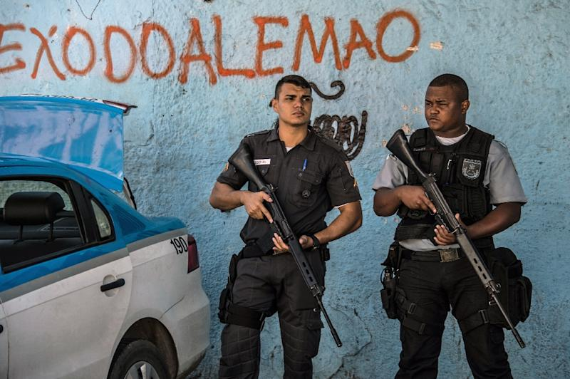 Police officers stand guard at Rio de Janeiro's Alemao favela on April 4, 2015