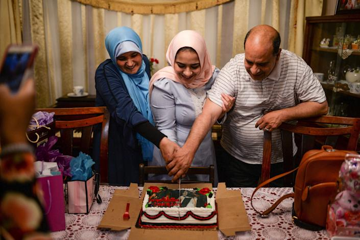 Dina Sayedahmed, a 22 year old Egyptian American Muslim with a major in journalism and political science from Rutgers University, cuts a cake with her parents as they celebrate her graduation and hold a Iftar feast at their family home during Ramadan in Bayonne, New Jersey, U.S. June 2, 2017. Picture taken June 2, 2017. REUTERS/Amr Alfiky