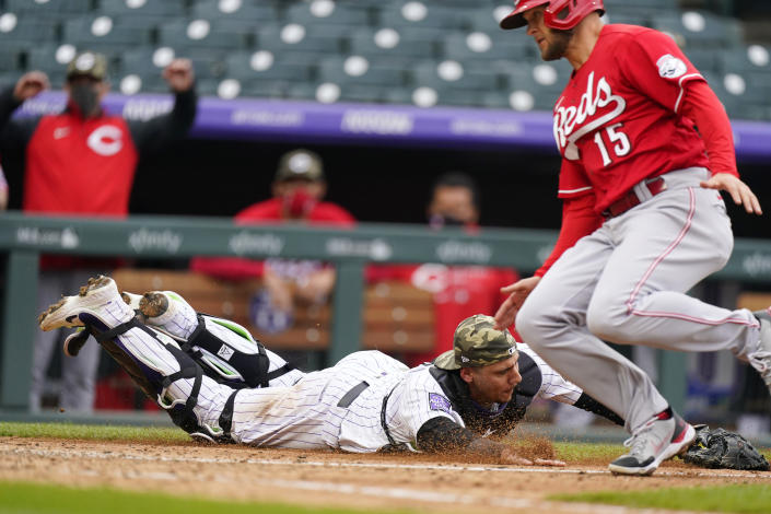 Colorado Rockies catcher Dom Nunez, left, reaches out to recover the ball after a wild pitch from reliever Jordan Sheffield (not shown) allowed Cincinnati Reds' Nick Senzel, right, to score from third base in the ninth inning of a baseball game Sunday, May 16, 2021, in Denver. (AP Photo/David Zalubowski)