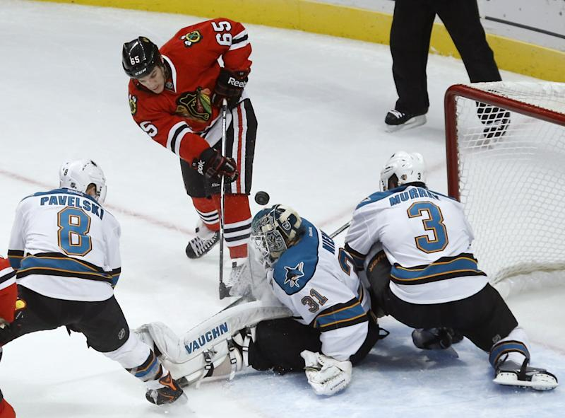 Chicago Blackhawks center Andrew Shaw (65) shoots and scores past San Jose Sharks goalie Antti Niemi and defenseman Douglas Murray (3) as center Joe Pavelski (8) watches during the second period of an NHL hockey game Friday, Feb. 15, 2013, in Chicago. (AP Photo/Charles Rex Arbogast)