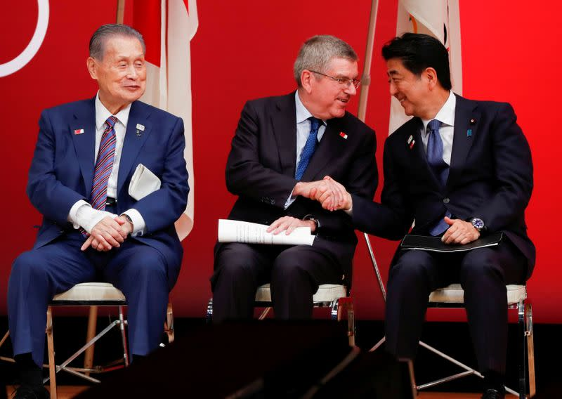 FILE PHOTO: IOC President Bach shakes hands with Japan's PM Abe during the 'One Year to Go' ceremony celebrating one year out from the start of the summer games in Tokyo