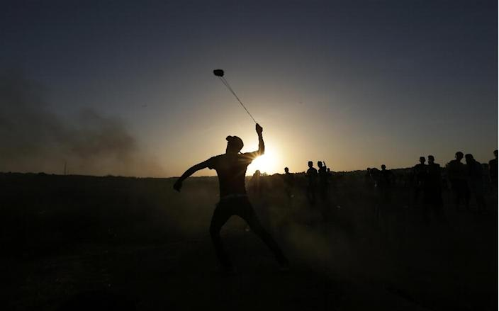 A masked Palestinian protester hurls a stone towards Israeli troops during clashes near a border fence between Israel and the Gaza Strip on October 14, 2015 east of Bureij in central Gaza (AFP Photo/Mahmud Hams)