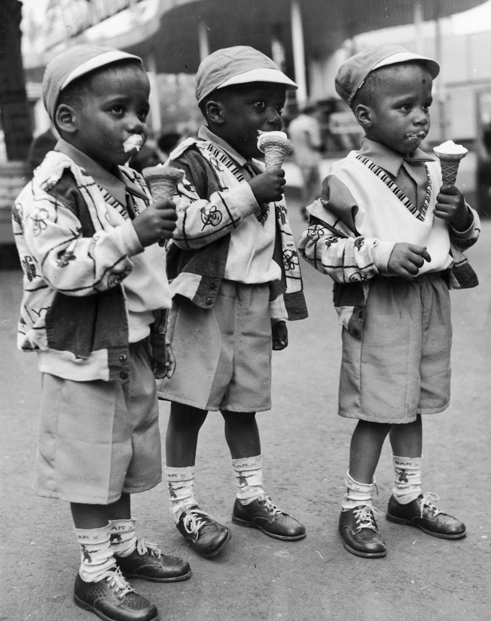 <p>A set of triplets wearing matching outfits dive right into their messy frozen treats.</p>