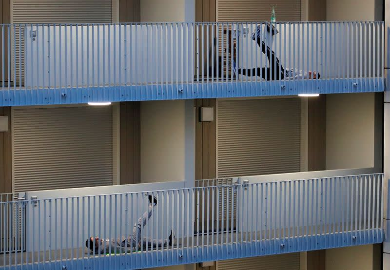 Residents exercise on their balconies following fitness trainers in Nantes