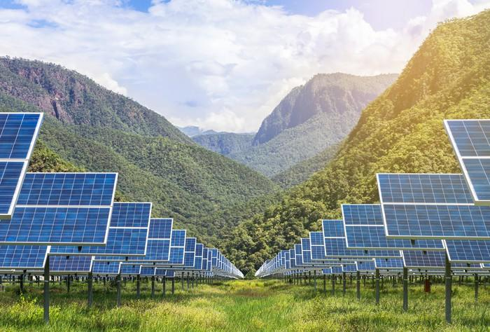 Solar panels with a mountainous background.