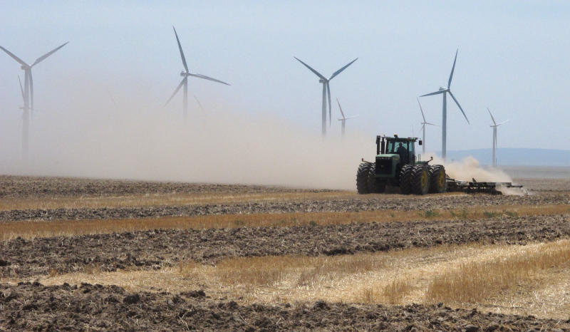 A farmer plows a field near wind turbines owned by Chicago-based Exelon Corp. outside of Mountain Home, Idaho on Thursday, Aug. 2, 2012. State electricity regulators aiming to set the course for Idaho's renewables industry for years to come will hold hearings next week on long-running and bitter disputes between utilities like Idaho Power Co. and independent wind, solar and biogas developers. The Idaho Public Utilities Commission has scheduled three days of hearings starting Tuesday, to be attended by a crowd of lawyers, utility executives and environmentalists. (AP Photo/John Miller)