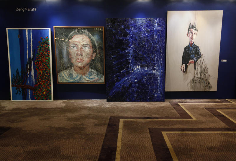 "Two paintings titled ""Portrait"", second from left, and ""Trauma"", right, by Chinese artist Zeng Fanzhi are displayed for sale at the Seoul Auction in Hong Kong Tuesday, April 3, 2012. Auctioneers in Hong Kong have sold 10 paintings seized from a South Korean bank that collapsed last year amid a corruption scandal to raise $2.4 million to help repay depositors. The paintings included works by noted Chinese artists Zeng and Zhang Xiaogang and American Julian Schnabel. (AP Photo/Kin Cheung)"
