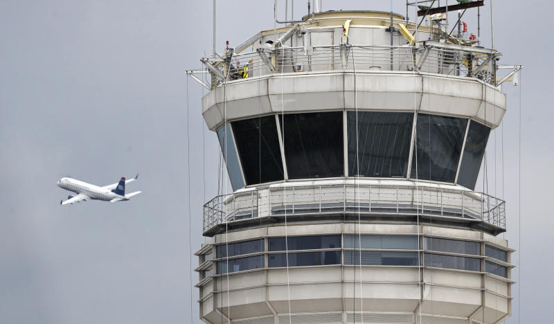 A passenger jet flies past the FAA control tower at Washington's Ronald Reagan National Airport, Thursday, March 24, 2011. A control tower supervisor who was unavailable to aid two airliners that landed at the airport this week has been suspended from his operational duties pending an investigation, the top U.S. aviation official said Thursday. (AP (AP Photo/Cliff Owen)