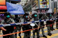 Riot police stand in line as anti-national security law protesters march at the anniversary of Hong Kong's handover to China from Britain in Hong Kong