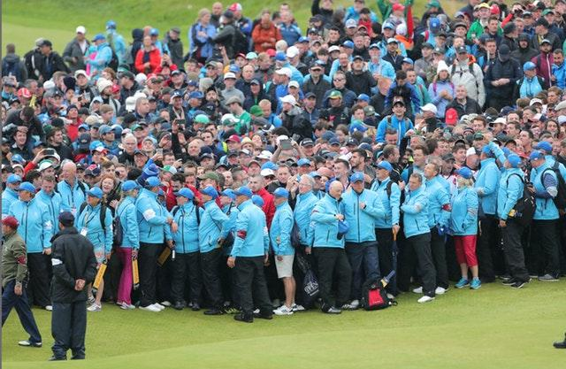 Large crowds gather around the 18th green