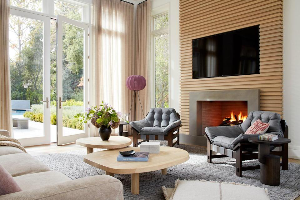 In the Atherton home, the abundant fireplaces provide another level of coziness. Two Lawson-Fenning Ojai lounge chairs and a Poltrona Frau Let It Be sofa, upholstered with Great Plains Lionheart fabric, surround two Stahl + Band L Series tables. The Moroccan wool rug by Marc Phillips and A+R Store Knit-Wit floor lamp lend another dose of texture and color.