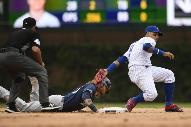 Milwaukee Brewers' Ben Gamel left, slides safely into second base as Chicago Cubs shortstop Javier Baez right, attempts to apply the tag during the ninth inning of a baseball game Saturday, Aug 31, 2019, in Chicago. Milwaukee won 2-0. (AP Photo/Paul Beaty)