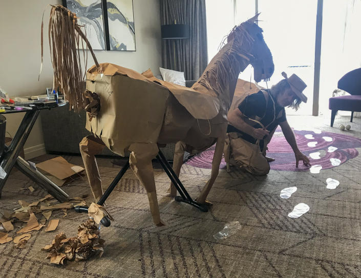 CORRECTS NAME - David Marriott poses with his paper horse Russell in his hotel room in Brisbane, Australia, April 3, 2021. While in quarantine inside his Brisbane hotel room, the art director was bored and started making a cowboy outfit from the paper bags his meals were being delivered in. His project expanded to include a horse and a clingfilm villain that he has daily adventures with, in images that have gained a huge online following. (David Marriott via AP)