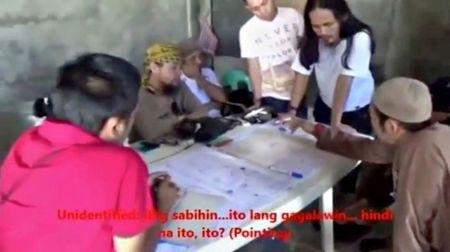 FILE PHOTO: Men identified by Philippines Intelligence officers as Isnilon Hapilon (2nd L, yellow headscarf) and Abdullah Maute (2nd R, standing, long hair) are seen in this still image taken from video released by the Armed Forces of the Philippines on June 7, 2017.    Armed Forces of the Philippines/Handout via REUTERS TV/File Photo