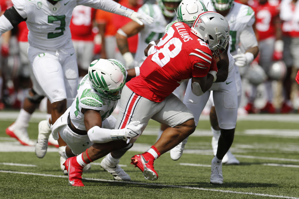 Ohio State running back Miyan Williams, center, is tackled by Oregon defenders Bradyn Swinson, left, and defensive back Verone McKinley during the first half of an NCAA college football game Saturday, Sept. 11, 2021, in Columbus, Ohio. (AP Photo/Jay LaPrete)