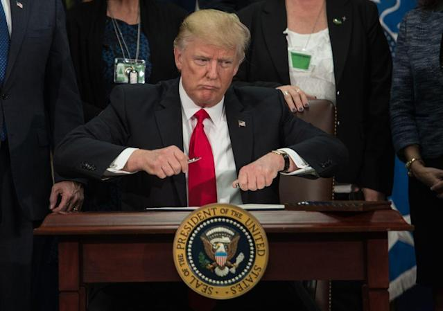 President Donald Trump takes the cap off a pen to sign an executive order to start the Mexico border wall project at the Department of Homeland Security facility in Washington, D.C., on January 25.