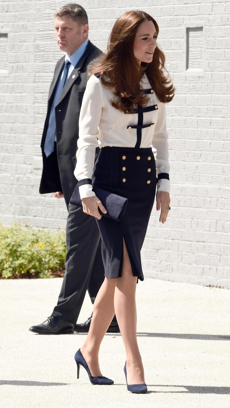 <p>The Duchess visited Bletchley Park in Alexander McQueen separates featuring a military-inspired shirt and slitted skirt. Kate accessorised with a blue suede Stuart Weitzman bag and matching heels. </p><p><i>[Photo: PA]</i></p>