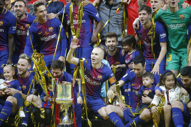 FC Barcelona's Andres Iniesta, centre, with teammates as they celebrate during an award ceremony after defeating Sevilla 5-0 in the Copa del Rey final soccer match at the Wanda Metropolitano stadium in Madrid, Spain, Saturday, April 21, 2018. (AP Photo/Paul White)