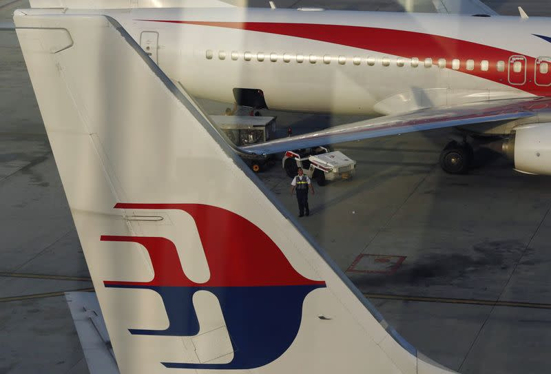 An airport worker walks between Malaysia Airlines planes at Kuala Lumpur International Airport